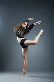 Tancerka w nowoczesnym stylu pozuje na szarym tle studyjnym