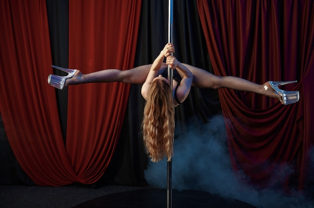 Tancerka z perfekcyjnym rozciąganiem, tańcem na rurze, tancerką striptizu. atrakcyjna striptizerka, taniec erotyczny, występy poledance, gorąca dziewczyna tańcząca w klubie ze striptizem