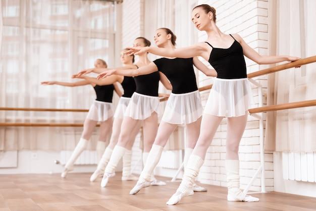 Tancerki baletowe dla dziewcząt ćwiczą w klasie baletowej.