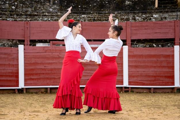 Tancerki flamenco w czerwonych sukienkach pokazujących swoje buty.