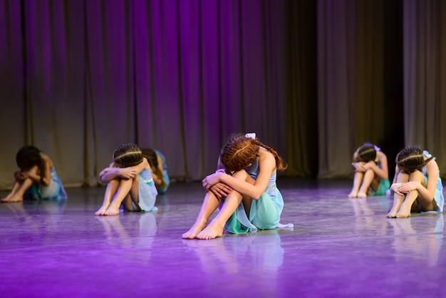 Tancerki siedzą na scenie, dramatycznie tańczą
