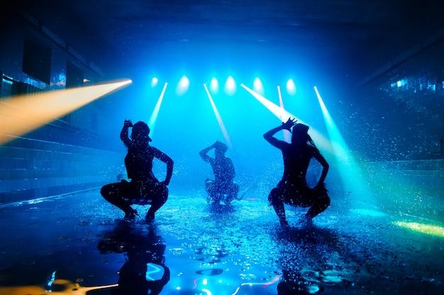 Tancerki tańczą na wodzie w pięknym świetle.