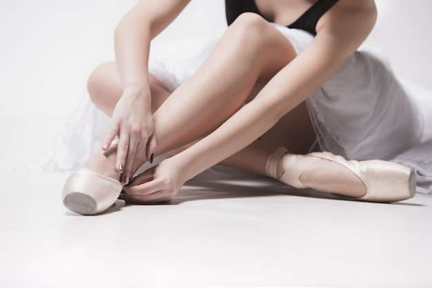 Tancerz baleriny siedzi ze skrzyżowanymi nogami