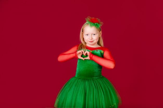 Tancerz dziecięcy zadowolony ze stroju koncertowego. moda dziecięca. modna zielona sukienka dla dzieci wygląda uroczo. koncepcja mody strojów tanecznych.