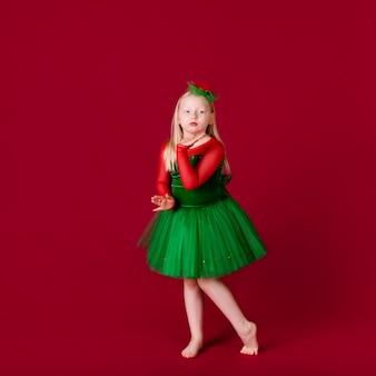 Tancerz dziecięcy zadowolony ze stroju koncertowego. moda dziecięca. modna zielona sukienka dla dzieci wygląda uroczo. odzież do tańca towarzyskiego