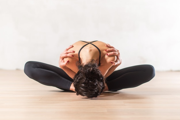 Tancerz robi zaawansowane ćwiczenia rozciągające motyla, siedząc pochylony do przodu, trzymając się za ramiona. młoda elastyczna kobieta w pięknej zmysłowej pozie.