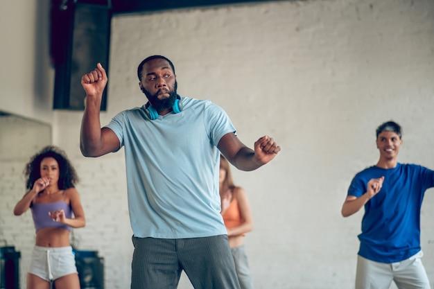 Tancerz, trening. emocjonalny brodaty młody człowiek ze słuchawkami na szyi, gestykuluje rękami w ruchu tanecznym
