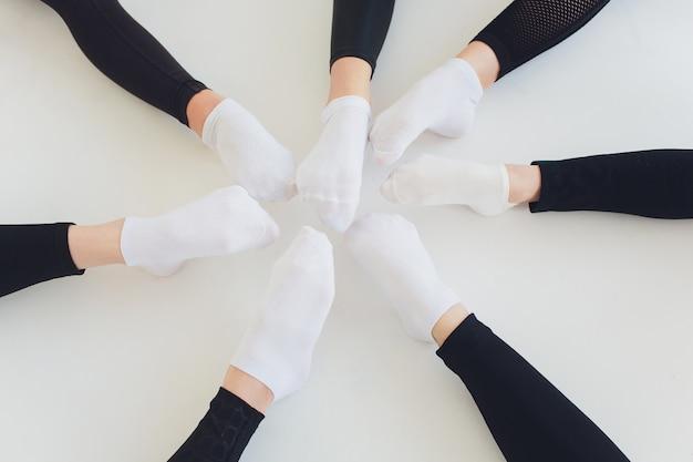Tancerz wiązanie butów baletowych. zamyka w górę baletniczej dziewczyny kładzenia na jej pointe butach siedzi na podłoga, zamazany tło.