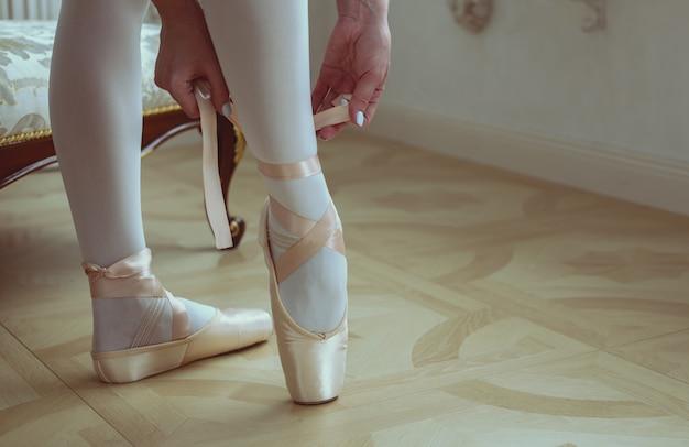 Tancerz wiązanie butów baletowych. zbliżenie.