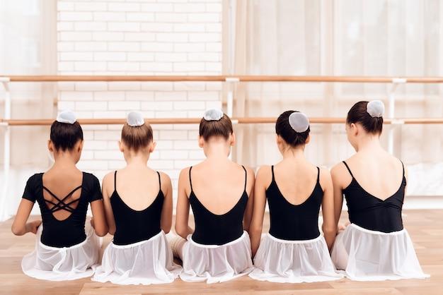 Tancerze dzieci siedzą w rzędzie z plecami do aparatu.