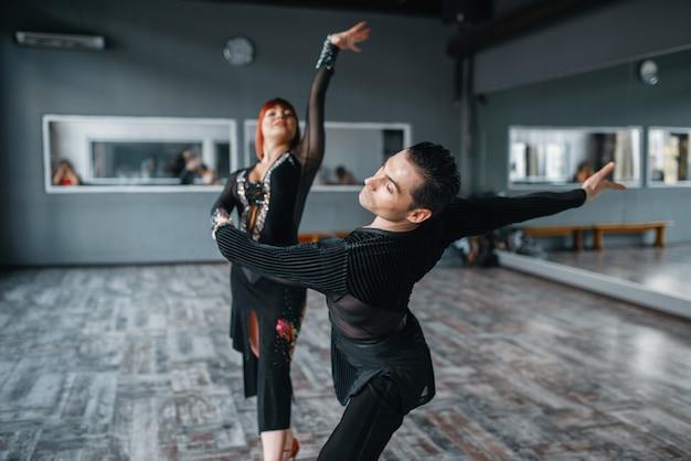 Tancerze elegancji w kostiumach na treningu tańca ballrom w klasie.