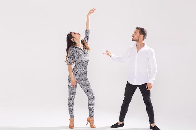 Tancerze salsy, kizomby, tanga i bachaty na białej ścianie z miejscem na kopię. koncepcja tańca społecznego