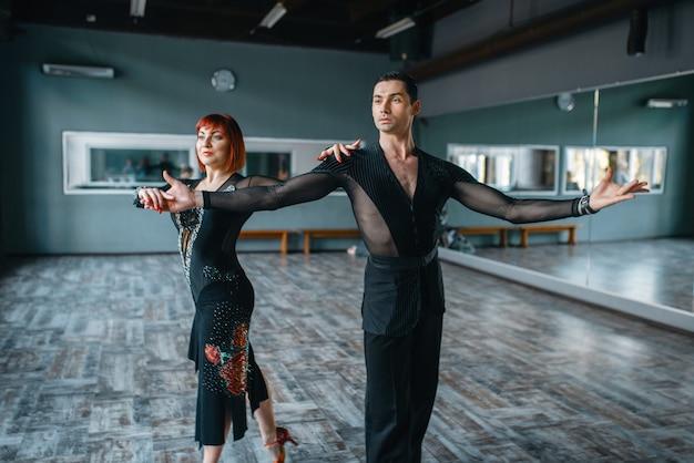 Tancerze w kostiumach na szkoleniu tańca towarzyskiego w klasie. partnerki płci żeńskiej i męskiej w profesjonalnym tańcu parowym w studio