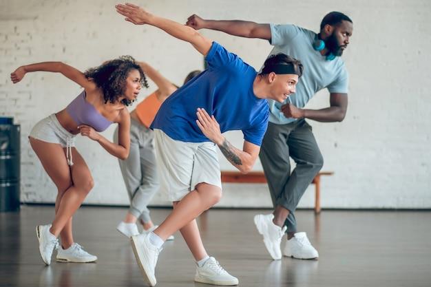 Tancerze, zespół. z profilu młodzi tancerze w trampkach ćwiczą razem, poruszając się synchronicznie