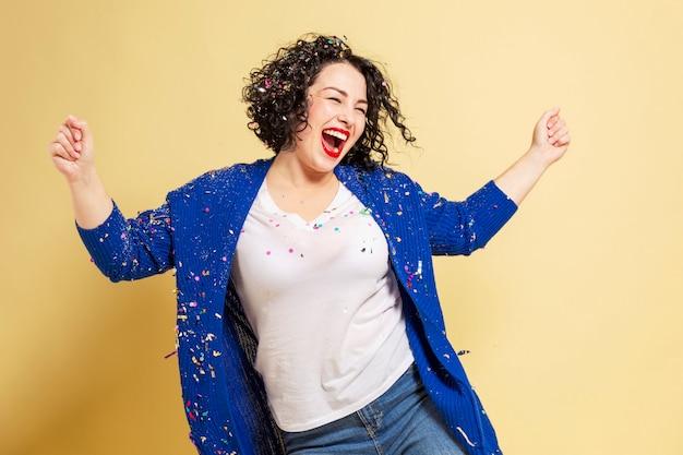 Tańcząc i śmiejąc się piękna młoda kobieta w dużych rozmiarach w dżinsach i niebieskim swetrze. żółta ściana.