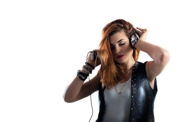 Tańcząca dziewczyna słucha muzyki z zestawu słuchawkowego i smartfona. na białym tle