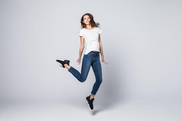 Tańcząca dziewczyna z brązowymi długimi włosami i szczęśliwy uśmiechnięty wyraz twarzy, skacząc w studio na białym tle