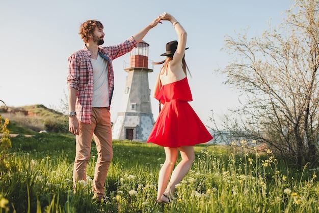 Tańcząca młoda stylowa para zakochana na wsi, indie hipster w stylu bohemy, weekendowe wakacje, letni strój, czerwona sukienka, zielona trawa, trzymanie się za ręce