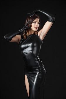 Tańcząca modelka ubrana w lateksowe ubrania.