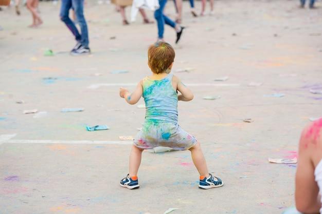 Tańczące dziecko z kolorowymi plecami i włosami na festiwalu holi