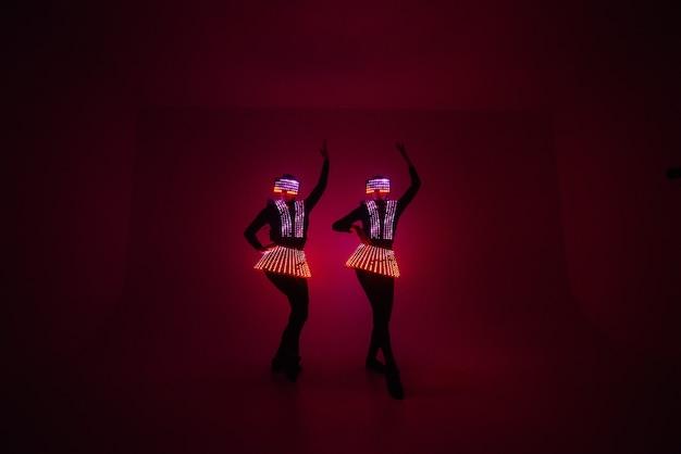 Tańczące dziewczyny w jasnych i kolorowych świetlistych strojach.