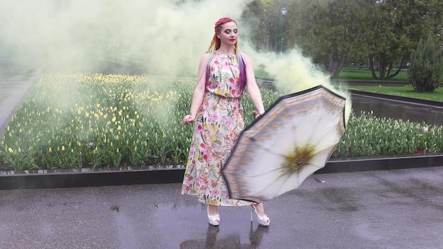 Tańczy dziewczyna z afrykańskimi warkoczami i makijażem w wiosennej sukience