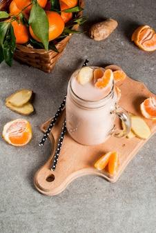 Tangerine smoothie z imbirem w słoiku kamieniarza, ze świeżymi surowymi mandarynkami, w szarej kamiennej tło odgórnego widoku kopii przestrzeni