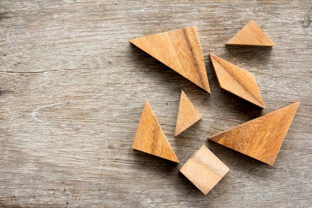 Tangram puzzle czekać na pełne na drewnianym stole tle
