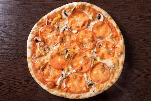 Tania pizza z pieczarkami, pomidorami i kukurydzą. w dowolnym celu.