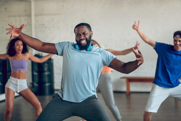 Taniec, emocje. emocjonalny afroamerykanin brodaty mężczyzna ze słuchawkami i przyjaciółmi za próbami tańca w sali