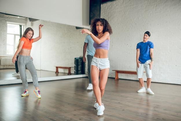 Taniec, hobby. skoncentrowane zaangażowane młode dziewczyny i facet wykonują taniec sportowy z trenerem