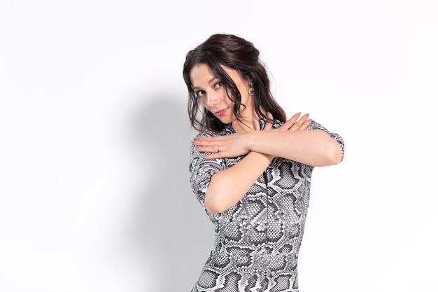 Taniec latynoski, taniec striptizowy, koncepcja damy współczesnej i bachata - kobieta tańczy improwizację i porusza długimi włosami na białej ścianie.