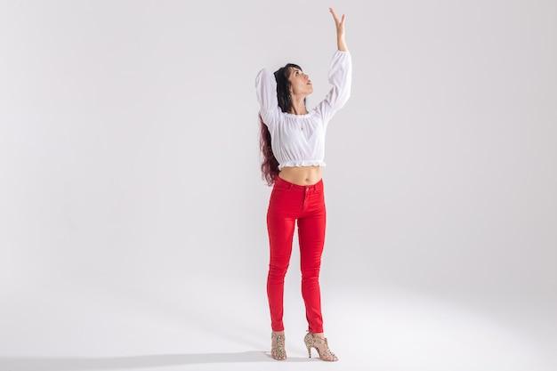 Taniec latynoski, taniec ze striptizem, koncepcja współczesna i bachata lady - kobieta tańcząca improwizację i poruszająca długimi włosami na białym tle z miejscem na kopię