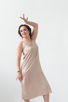 Taniec latynoski, taniec ze striptizem, koncepcja współczesna i bachata lady - kobieta tańcząca improwizację i poruszająca długimi włosami na białym tle.