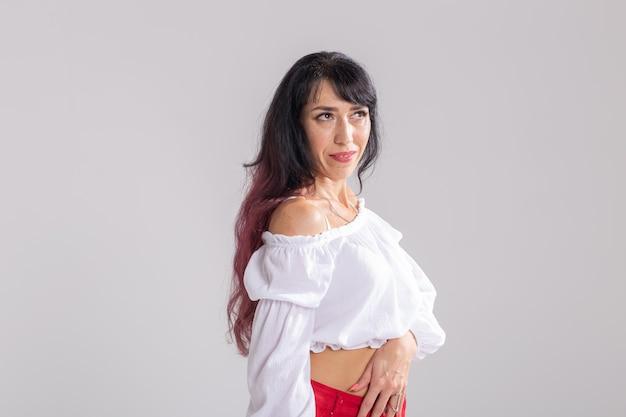 Taniec latynoski, taniec ze striptizem, koncepcja współczesna i bachata lady - kobieta tańcząca improwizację i poruszająca długimi włosami na białym tle