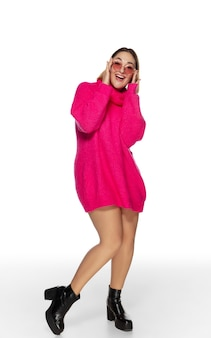 Taniec. piękna młoda kobieta jasny różowy wygodny sweter, długi rękaw na białym tle na tle białego studia. styl magazynu, moda, koncepcja piękna. modne pozowanie. miejsce na reklamę.