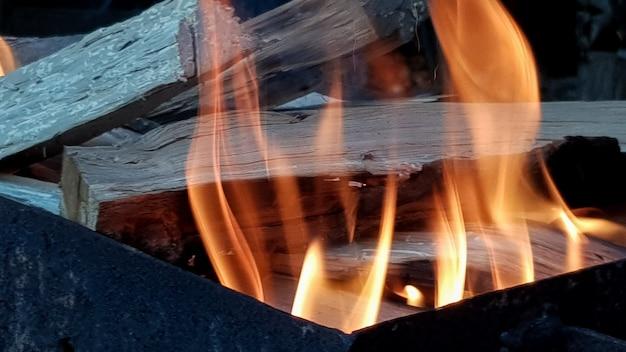 Taniec płomieni, grill na otwartym ogniu. ogień w grillu z płonącym drewnem. przygotuj węgiel drzewny przed grillowaniem mięsa lub ryb na świeżym powietrzu. płomień w kominku. przygotowanie grilla.