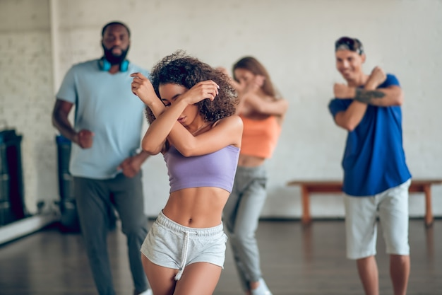 Taniec, próba. młoda szczupła dziewczyna z ciemnymi kręconymi włosami podczas próby z przyjaciółmi