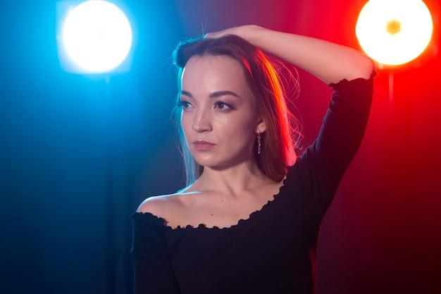 Taniec społeczny, koncepcja ludzi - młoda kobieta sexy tańczy w ciemności i cieszy się.