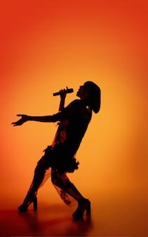 Taniec. sylwetka młodej wokalistki na białym tle na pomarańczowym tle studio gradientu w świetle neonowym. piękny cień w akcji, występy. pojęcie ludzkich emocji, ekspresji, reklamy, muzyki, sztuki.