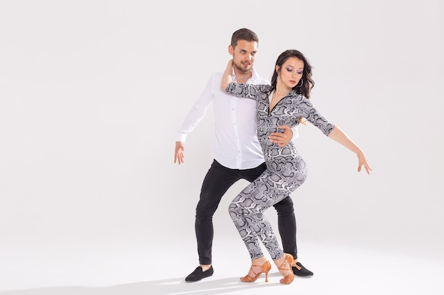 Taniec towarzyski, bachata, kizomba, zouk, koncepcja tanga - mężczyzna przytula kobietę podczas tańca na białej ścianie z miejscem na kopię