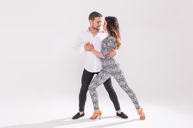Taniec towarzyski, bachata, kizomba, zouk, koncepcja tanga - mężczyzna przytula kobietę podczas tańca na białym