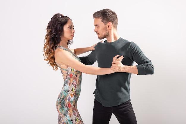 Taniec towarzyski, kizomba, tango, salsa, koncepcja ludzi - piękna para tańczy bachatę na białej ścianie z miejscem na kopię