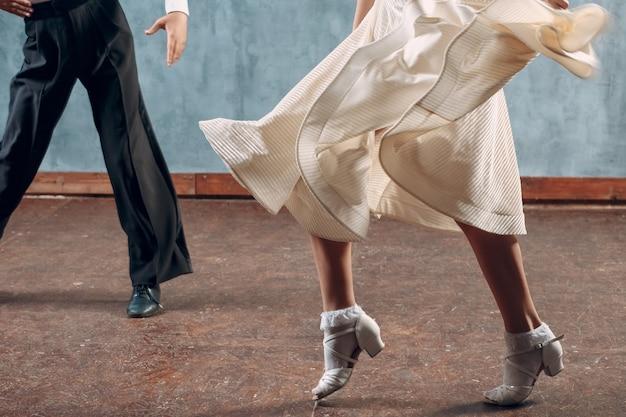 Taniec towarzyski. młoda para tancerzy towarzyskich. taniec latynoamerykański i tancerka