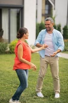 Taniec w pobliżu domu. ciemnowłosa kochająca żona w dżinsach tańcząca z mężem w pobliżu domku
