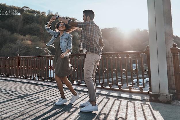 Taniec w rytmie miłości. pełna długość pięknej młodej pary trzymającej się za ręce i kręcącej się