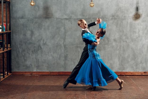 Taniec w sali balowej. młoda para tańczy walca w studio.