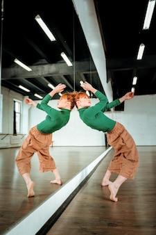 Taniec współczesny. rudowłosa profesjonalna nauczycielka tańca w zielonym golfie ćwicząca ruchy taneczne