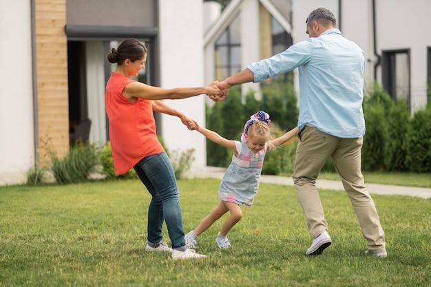 Taniec z rodzicami. śliczna mała córeczka czuje się szczęśliwa podczas tańca na zewnątrz z rodzicami