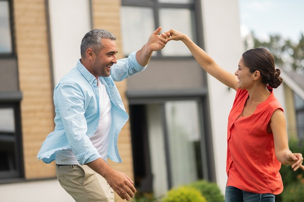 Taniec z żoną na zewnątrz. siwowłosy kochający i troskliwy mąż tańczący z żoną na zewnątrz
